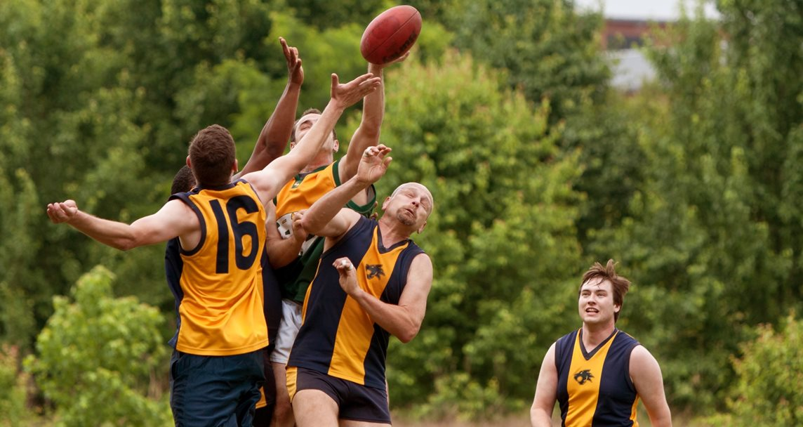 Several players jump to catch the ball in an amateur club game of Australian Rules Football