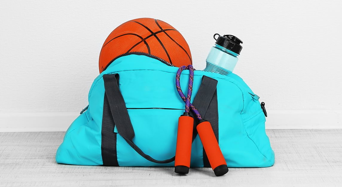 Blue bag containing sports gear, including a basketball, skipping rope and water bottle